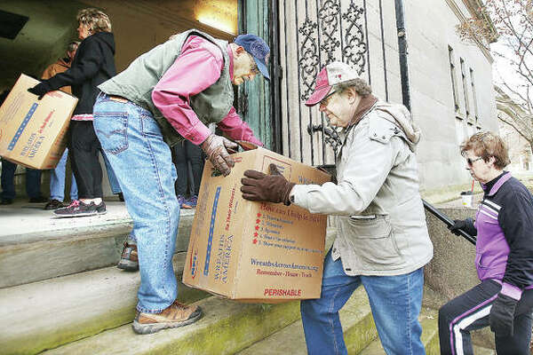 Volunteers form a chain to unload boxes holding 702 wreaths Wednesday into the Grand View Mausoleum in Alton City Cemetery, where they will be stored until placed on veterans' graves in the adjacent Alton National Cemetery as part of a national Wreaths Across America program this Saturday.
