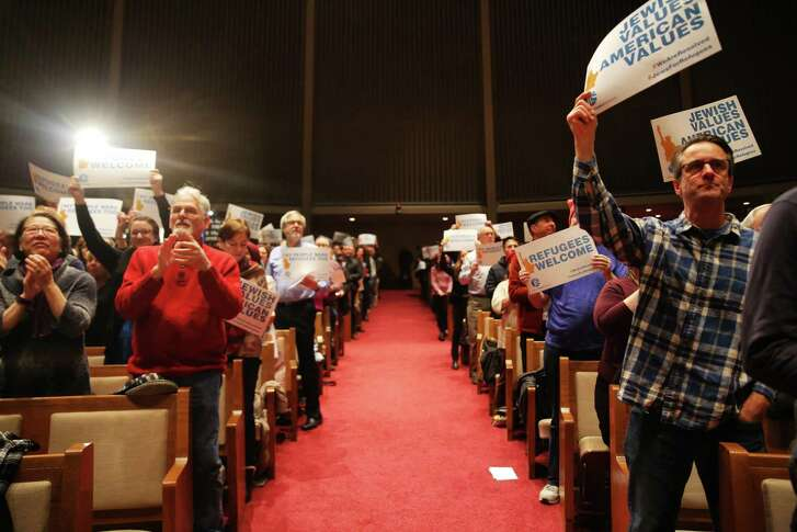 People raise their signs and hands in support of immigrants during the Jewish Rally for Refugees at Temple de Hirsch Sinai in Washington state.
