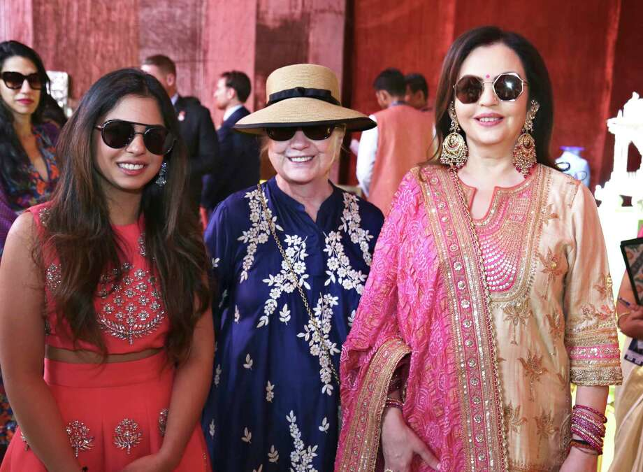 In this Sunday, Dec. 9, 2018 handout photo released by Reliance Industries Limited, former U.S. Secretary of State Hillary Clinton stands and Nita Ambani, right, visit a curated showcase of traditional Indian crafts and art forms on display ahead of the wedding of Isha Ambani, left, in Udaipur, India. Isha Ambani, the daughter of India's richest mogul, is to wed Anand Piramal, the son of one of India's biggest industrialists, at the Ambani estate in Mumbai on Wednesday, capping off an extravagant days-long event. (Reliance Industries Limited via AP) / Reliance Industries Limited