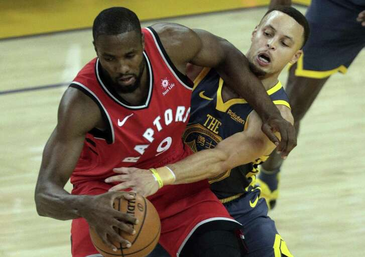 Stephen Curry (30) defends against Serge Ibaka (9) in the first half as the Golden State Warriors play the Toronto Raptors at Oracle Arena in Oakland, Calif., on Wednesday, December 12, 2018.