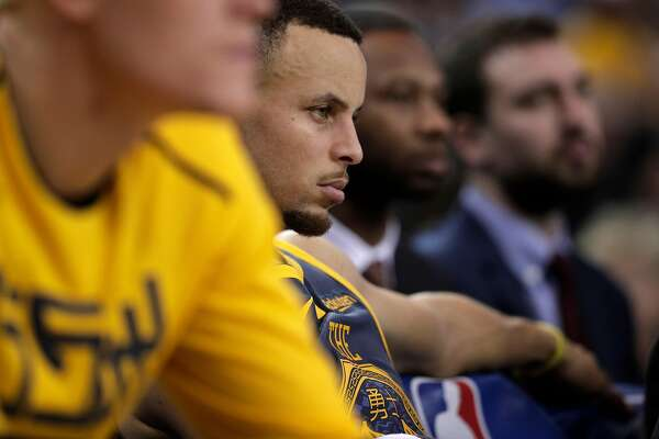 Stephen Curry (30) on the bench late in the second half as the Golden State Warriors play the Toronto Raptors at Oracle Arena in Oakland, Calif., on Wednesday, December 12, 2018.
