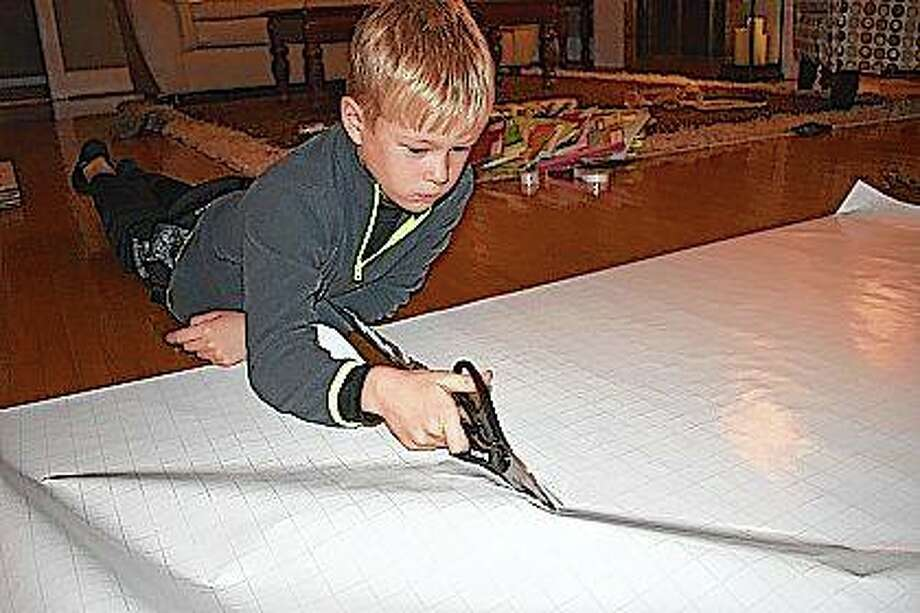 Beckham Oldenettel prepares paper to cover his Beckham's Bookshelf boxes. Photo: Photo Provided