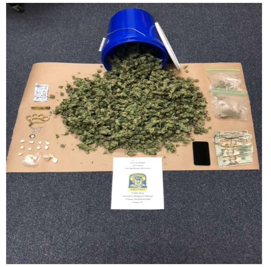 "A green Mazda 626 with Maine plates that was ""parked crookedly in a parking spot"" at the Darien rest area lead to a significant drug buston Tuesday, Dec. 11, 2018. Troopers approached the vehicle and began speaking with the occupants, who couldn't provide answers to simple questions. The trooper noted several physical indicators of drug use on both occupants. A search of the vehicle found 2.6 pound of marijuana, 19.3 grams of ""crack"" cocaine and 13.7 grams of heroin. Photo: Connecticut State Police Photo"
