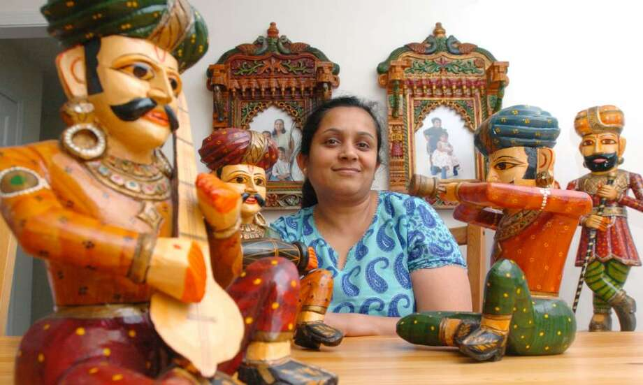 Radhika Jain, of New Milford, is shown with Indian items that she sells out of her home. The items shown are called jhrokhas, dwar pal and musicians photographed July 7, 2010. Photo: Chris Ware / The News-Times