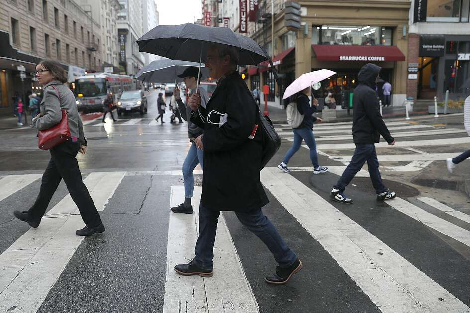 Jim Klatami (middle) from San Francisco walks with his umbrella as it starts to rain on Powell St. on Tuesday, Nov. 27, 2018, in San Francisco, Calif.