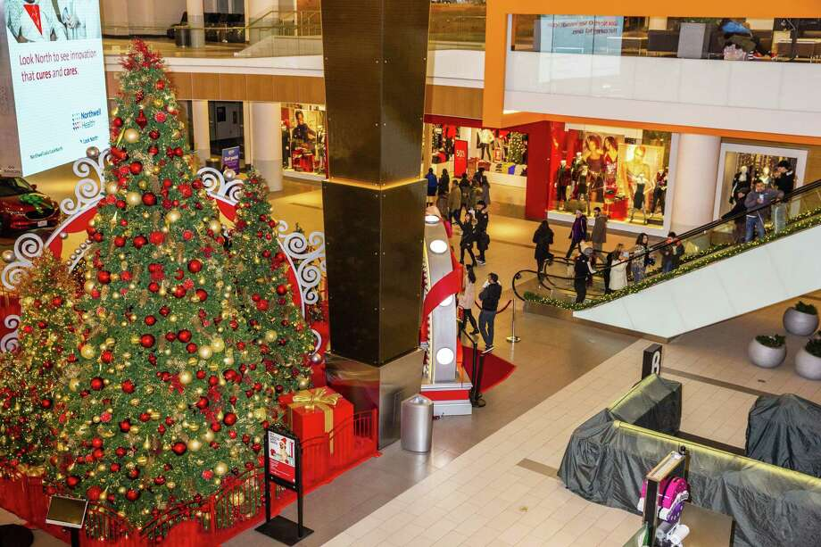 Shoppers walk past Christmas trees and decorations at the Simon Property Group Roosevelt Field mall in Garden City, New York, U.S., on Nov. 22, 2018. Photo: Bloomberg Photo David Williams / Bloomberg