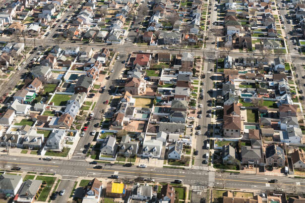 An aerial view of suburban detached houses and streets in New York City.