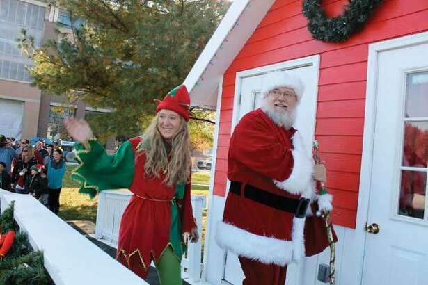 Santa Claus and his helper smile at the crowd during a previous Santa at City Park event. The event has started this year in Edwardsville and is among many activities hosted in the city during the holiday season.