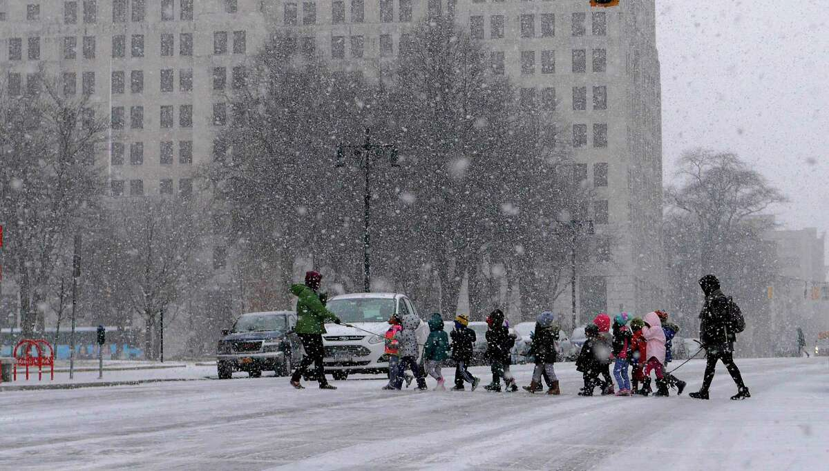 Children are led across Washington Ave. as a snow squall came through on Thursday, Dec. 13, 2018, in Albany, N.Y. (Paul Buckowski/Times Union)