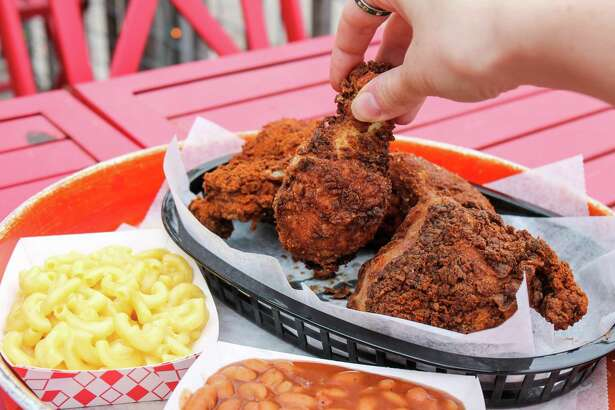 Half of a fried San Antonio Hot Chicken with side dishes at Shuck Shack.