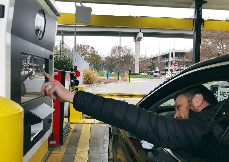 A rental car driver demonstrates a new biometric scanning machine by placing his finger on the reader at the Hertz facility at Hartsfield-Jackson Atlanta International Airport. Photo: Jeff Martin / Associated Press
