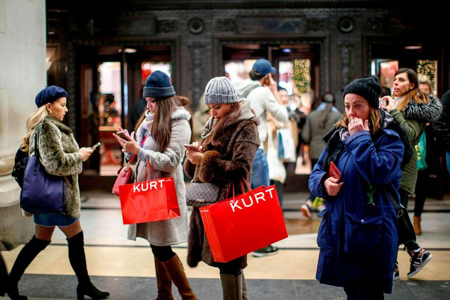 Shoppers scan their smartphones in the main retail district on Oxford Street in London less than two weeks before Christmas. Retailers are using apps to improve shoppers' experience in stores. Photo: Tolga Akmen / AFP / Getty Images