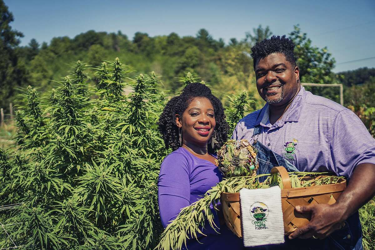 """In this September 2018 photo provided by Clarenda """"Cee"""" Stanley-Anderson, Stanley-Anderson and her husband, Malcolm Anderson Sr., pose for pictures of their hemp-farming business, Green Heffa Farms, Inc., in Liberty, N.C. Hemp is about to get the federal legalization that marijuana, its cannabis cousin, craves. That unshackling at the national level sets the stage for greater expansion in an industry seeing explosive growth through demand for CBDs, the non-psychoactive compound in hemp that many see as a way to better health. (Donald Rex Bishop/Green Heffa Farms, Inc. via AP)"""
