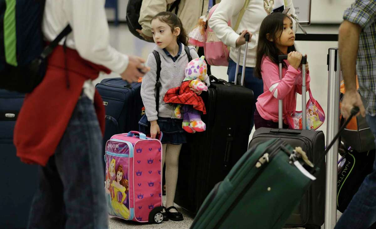 Alisson Castro, 5, left, and Meah Orellana, 6, right, both of Houston wait with their families to check in for flights in Terminal A at Bush Intercontinental Airport Thursday, Dec. 13, 2018, in Houston.