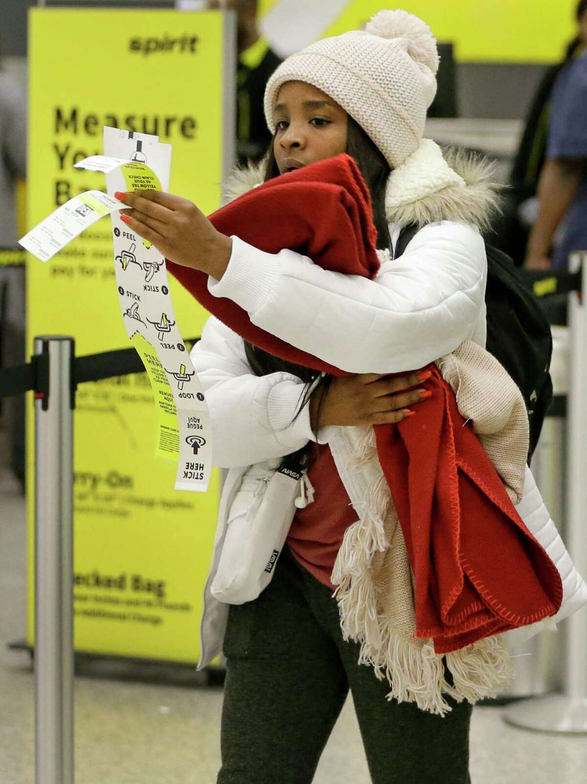 Danasia Helaire of Lafayette juggles her baggage tags as she check in for a flight to Colorado with her family in Terminal A at Bush Intercontinental Airport Thursday, Dec. 13, 2018, in Houston.