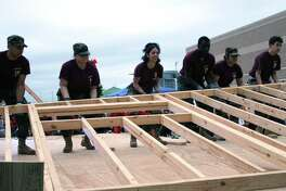 Summer Creek High School JROTC and Builder students raise a wall to continue the construction of the tiny home designed for homeless veterans.