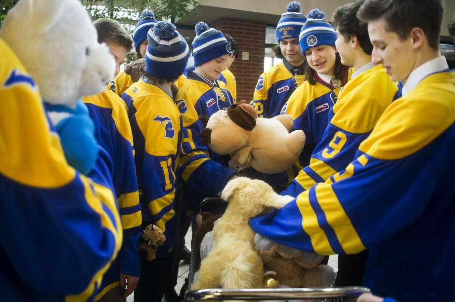 Midland High hockey players place stuffed animals into a cart before they are donated to patients in the pediatric unit at MidMichigan Medical Center-Midland on Wednesday, Dec. 12, 2018. (Katy Kildee/kkildee@mdn.net) Photo: (Katy Kildee/kkildee@mdn.net)