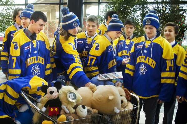 Midland High hockey players place stuffed animals into a cart before they are donated to patients in the pediatric unit at MidMichigan Medical Center-Midland on Wednesday, Dec. 12, 2018. (Katy Kildee/kkildee@mdn.net)