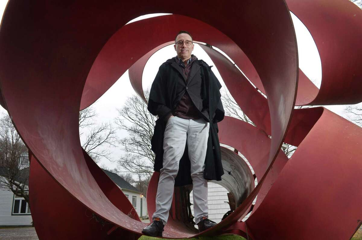 Fernando Alvarez, owner of Alvarez Gallery in Stamford, with the 30-foot-long, 12,000-pound sculpture by artist Charles O. Perry he recently acquired, on Thursday in Wilton. The sculpture had been an installation at the Stamford Town Center and was removed and essentially abandoned for a decade.