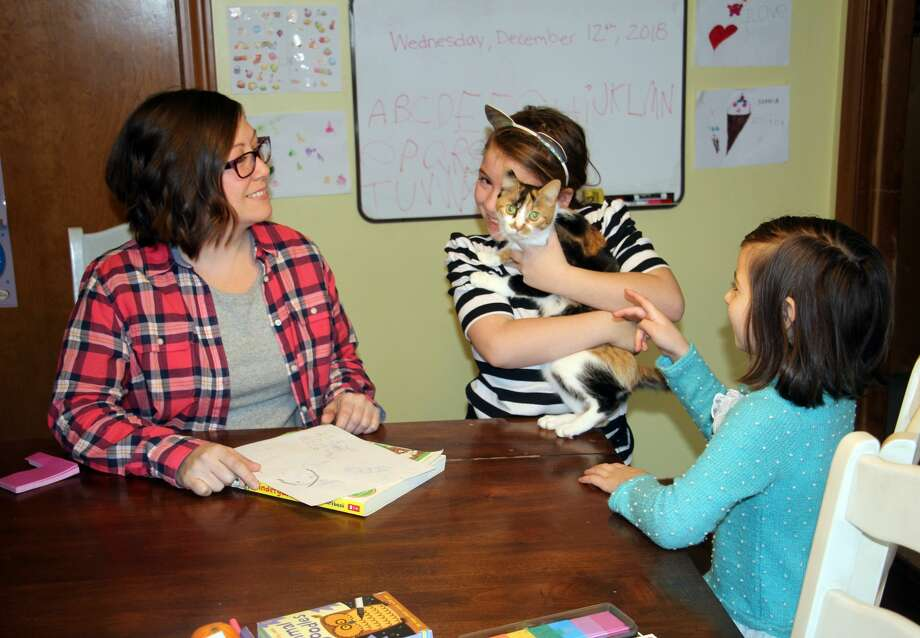 Shar Mohr (left) and two of her five children take a break from schoolwork one afternoon to play with their feline friend, Clover. Shar is a medical marijuana cardholder speaking out about her marijuana use now that it's been legalized for adult recreational use in the state of Michigan. Photo: Bradley Massman/Huron Daily Tribune