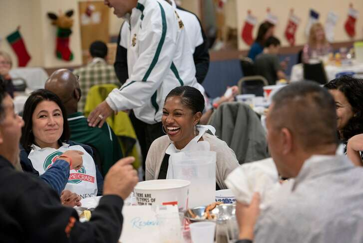 Guest Naima Calvillo, center, laughs with fellow diners during a crab dinner fundraiser held to support Castro Valley High School, at the Castro Valley Moose Lodge in Castro Valley, California, on Saturday, December 8, 2018.