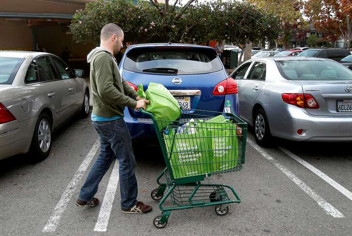 Yonatan Schkolnik brings his groceries to his car in the parking lot of Whole Foods for his Instacart delivery Monday November 10, 2014. Yonatan Schkolnik drives paying customers for Sidecar and delivers groceries for Instacart in the Bay Area.