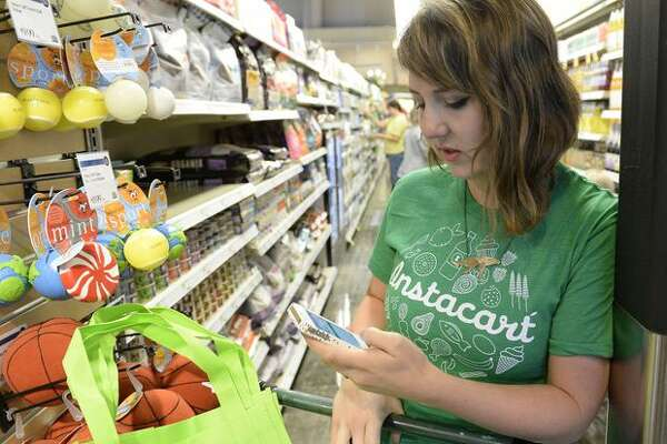 Kaitlin Myers, a shopper for Instacart, forages for a customer at a Whole Foods in Denver.