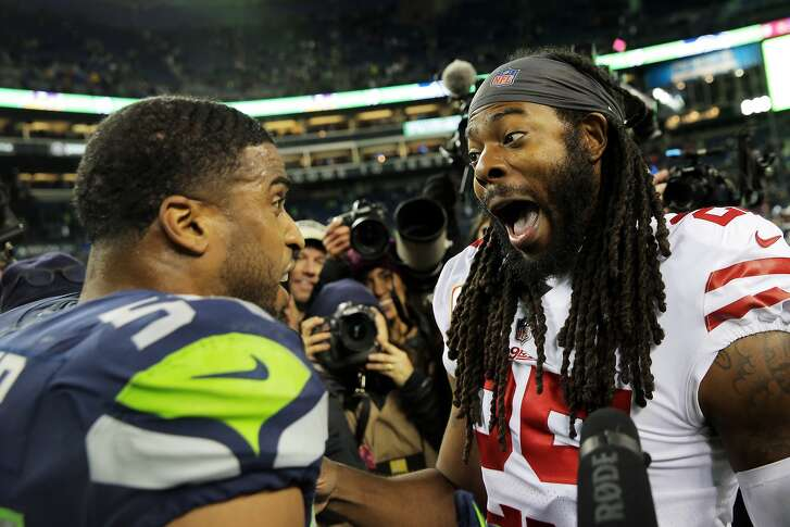 Former teammates San Francisco's Richard Sherman (25) and Seahawks linebacker Bobby Wagner joke around after their game, Sunday, Dec. 2, 2018 at CenturyLink Field.  (Genna Martin, seattlepi.com)