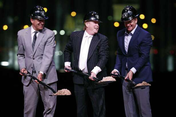 Raiders owner Mark Davis, center, poses for photographers beside Nevada Gov. Brian Sandoval, left, and NFL commissioner Roger Goodell during a ceremonial groundbreaking for the Oakland Raiders' stadium Monday, Nov. 13, 2017, in Las Vegas.