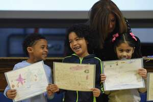 First-graders Joseph Marshall and Dominique Reyes show their underwater drawings as Lisa Gironda holds the microphone for kindergartener Adriana Velasquez to speak about her project during the Enrichment Clusters sharing assembly at Tracey School in Norwalk, Conn. Thursday, Dec. 13, 2018. Groups of students spent six weeks learning about a specific topic and shared their knowledge in short lessons and performances in front of the whole school on Thursday. Topics included poetry, quilting, yoga, watercolors, dance, newspapers, money management and more.
