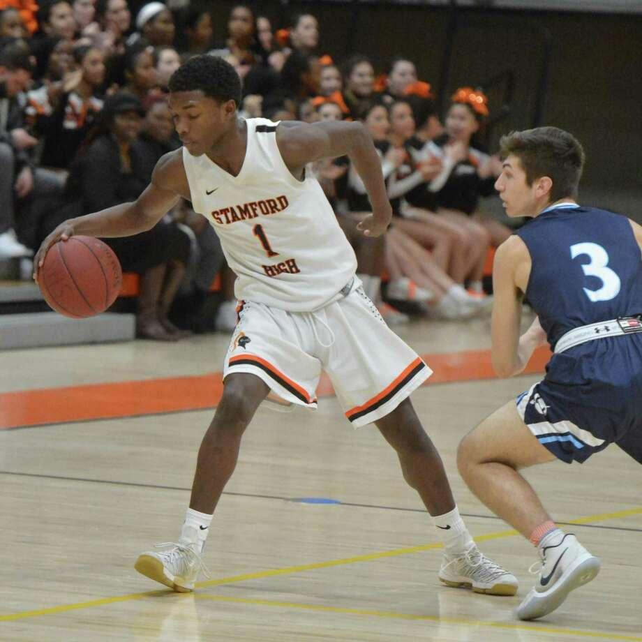 Stamford's Josh Thervil moves the ball around a defender against Wilton on Feb. 19. Photo: Alex Von Kleydorff / Hearst Connecticut Media / Norwalk Hour