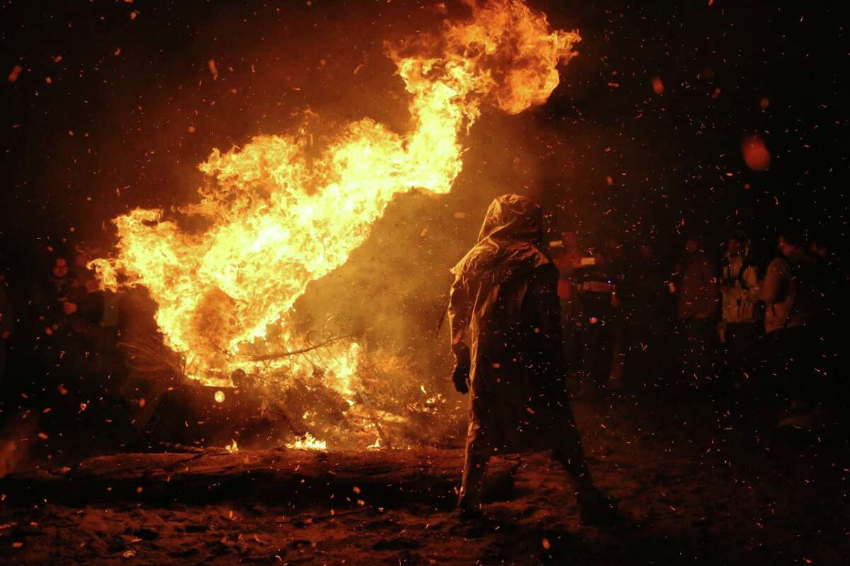The annual Point83 cyclist club Christmas tree burn, Thursday, Jan. 11, 2018 at Golden Gardens Beach Park. Participants bring their trees to the inferno, most via bicycle. The bonfire has become an annual tradition over the past decade.