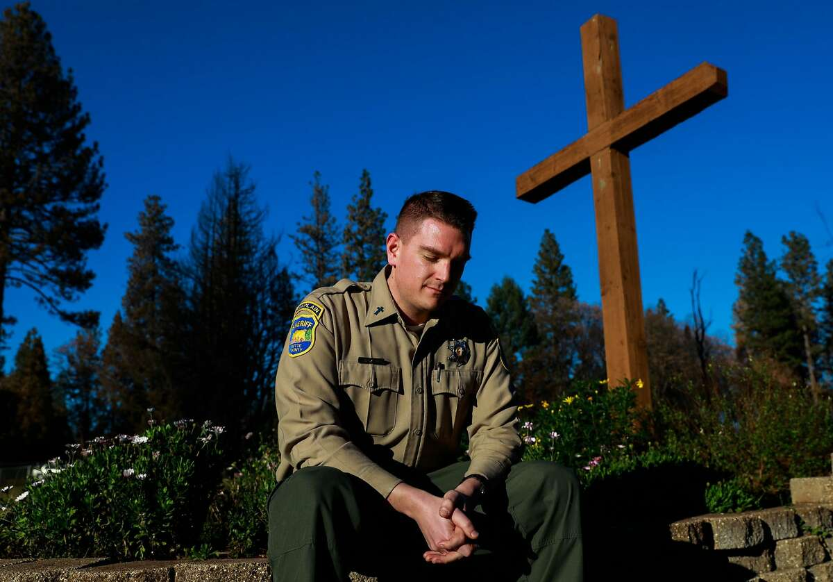 Butte County chaplain Jeremy Carr, 31 sits for a portrait at a Lutheran Church that burned down on Pentz Road in Paradise, California, on Thursday, Dec. 6, 2018. Jeremy remembers seeing the church after the Camp Fire and was struck by the wooden cross that was still standing despite the church burning down.