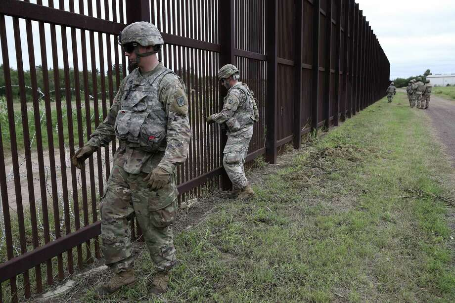Soldiers secure razor wire to the U.S.-Mexico border wall near downtown Brownsville in 2018. The president send more than 5,000 troops to the border before Thanksgiving last year. Photo: Jerry Lara / Staff Photographer / © 2018 San Antonio Express-News