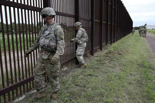 Soldiers secure razor wire to the U.S.-Mexico border wall near downtown Brownsville last month. The active-duty troops, numbering about 5,200 as of Monday, will begin returning home this week.
