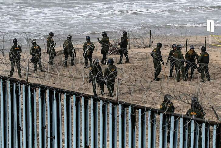 US border patrol agents stand guard as pro-migrants activists demonstrate against US migration policies near the US-Mexico border fence at Imperial beach in San Diego county, US, as seen from Playas de Tijuana, Baja California state, Mexico, on December 10, 2018. (Photo by Guillermo Arias / AFP)GUILLERMO ARIAS/AFP/Getty Images