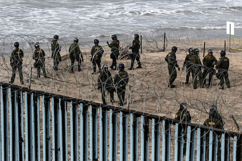 US border patrol agents stand guard as pro-migrants activists demonstrate against US migration policies near the US-Mexico border fence at Imperial beach in San Diego county, US, as seen from Playas de Tijuana, Baja California state, Mexico, on December 10, 2018.  Photo: Guillermo Arias / AFP / Getty Images