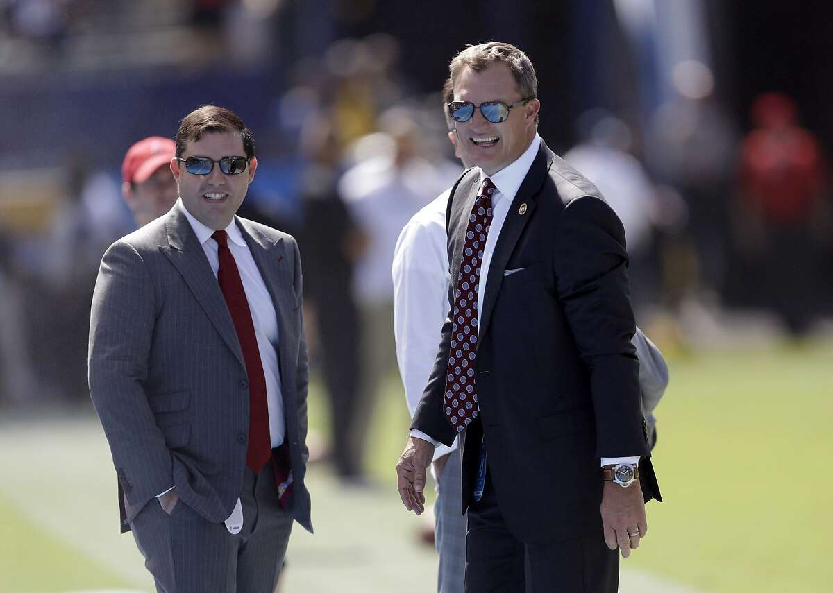 San Francisco 49ers owner Jed York, left, and general manager John Lynch stand on the field prior to an NFL football game against the Los Angeles Chargers, Sunday, Sept. 30, 2018, in Carson, Calif. (AP Photo/Marcio Sanchez)