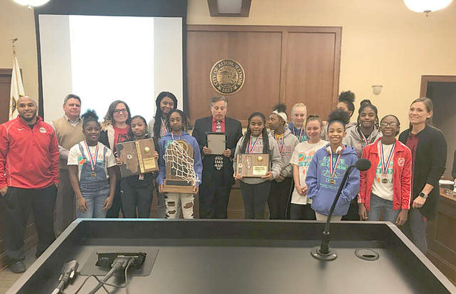 """Mayor Brant Walker reads a proclamation at Alton City Council deeming Dec. 12, 2018 as """"Alton Middle School Junior Redbirds Day,"""" while members of the Alton Middle School girls' basketball team hold their multiple trophies. Photo: Riley Newton 