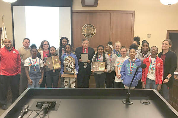 "Mayor Brant Walker reads a proclamation at Alton City Council deeming Dec. 12, 2018 as ""Alton Middle School Junior Redbirds Day,"" while members of the Alton Middle School girls' basketball team hold their multiple trophies."