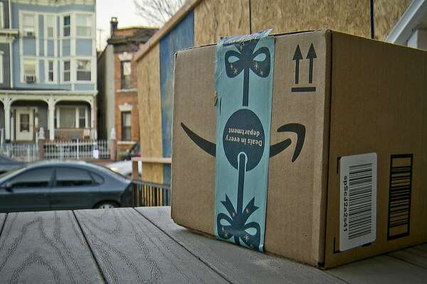 This image taken from video shows an Amazon package containing a GPS tracker on the porch of a Jersey City, N.J. residence after its delivery Tuesday, Dec. 11, 2018. The explosion in online shopping has led to porch pirates and stoop surfers swiping holiday packages from unsuspecting residents. The cops in one New Jersey city are trying to catch the thieves with some trickery of their own. (AP Photo/Robert Bumsted)