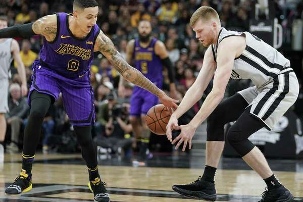 Los Angeles Lakers' Kyle Kuzma (0) reaches for the ball next to San Antonio Spurs' Davis Bertans during the first half of an NBA basketball game Friday, Dec. 7, 2018, in San Antonio. San Antonio won 133-120. (AP Photo/Darren Abate)