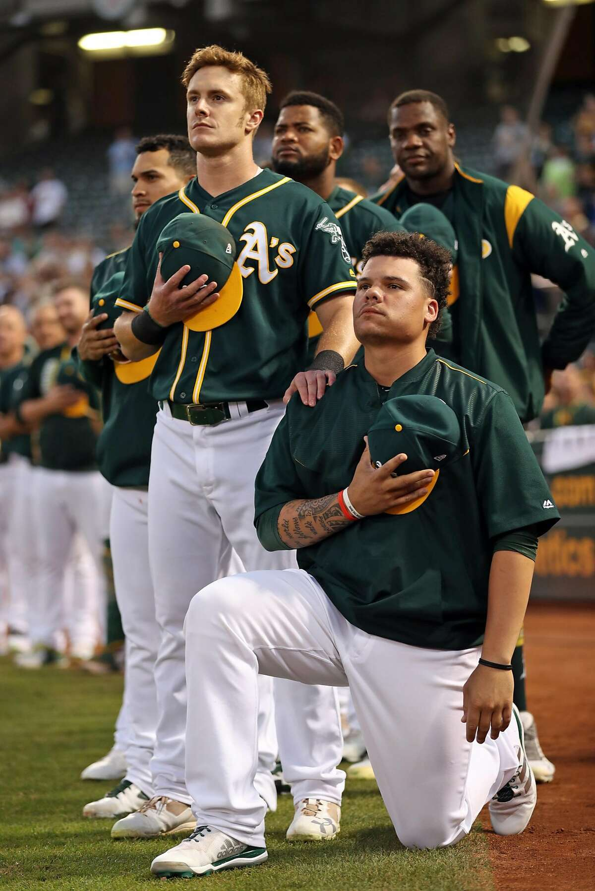 Oakland Athletics' Bruce Maxwell kneels during the National Anthem as teammate, Mark Canha, flanks him before A's play Seattle Mariners' during MLB game at Oakland Coliseum in Oakland, Calif., on Tuesday, September 26, 2017.