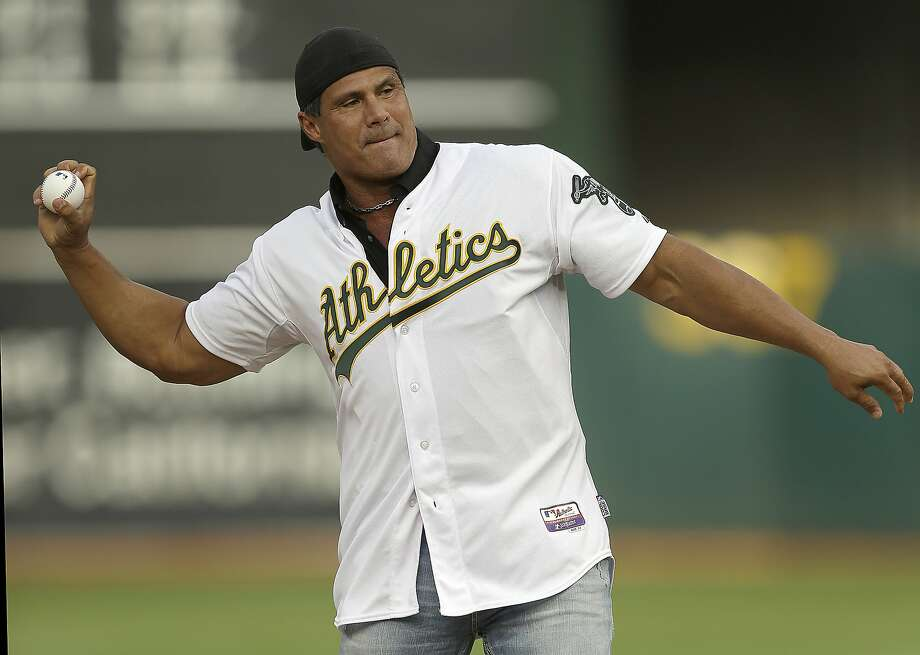 """FILE - In this Sept. 3, 2016, file photo, former Oakland Athletics player Jose Canseco throws out the ceremonial first pitch prior to a baseball game against the Boston Red Sox in Oakland, Calif. Canseco, a former major league slugger, has made his pitch for a big job at the White House, tweeting Wednesday, Dec. 12, 2018, to U.S. President Donald Trump: """"u need a bash brother for Chief if (sic) Staff."""" (AP Photo/Ben Margot, File) Photo: Ben Margot / Associated Press"""