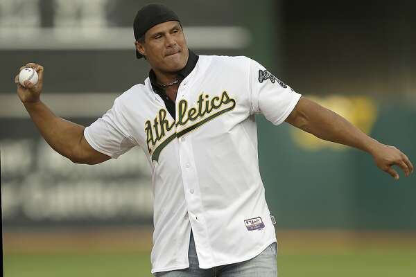 "FILE - In this Sept. 3, 2016, file photo, former Oakland Athletics player Jose Canseco throws out the ceremonial first pitch prior to a baseball game against the Boston Red Sox in Oakland, Calif. Canseco, a former major league slugger, has made his pitch for a big job at the White House, tweeting Wednesday, Dec. 12, 2018, to U.S. President Donald Trump: ""u need a bash brother for Chief if (sic) Staff."" (AP Photo/Ben Margot, File)"