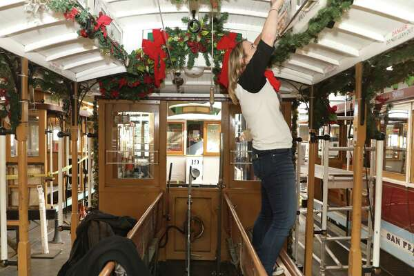 Chronicle columnist Heather Knight decorates a cable car with copies of historic Chronicle front pages.