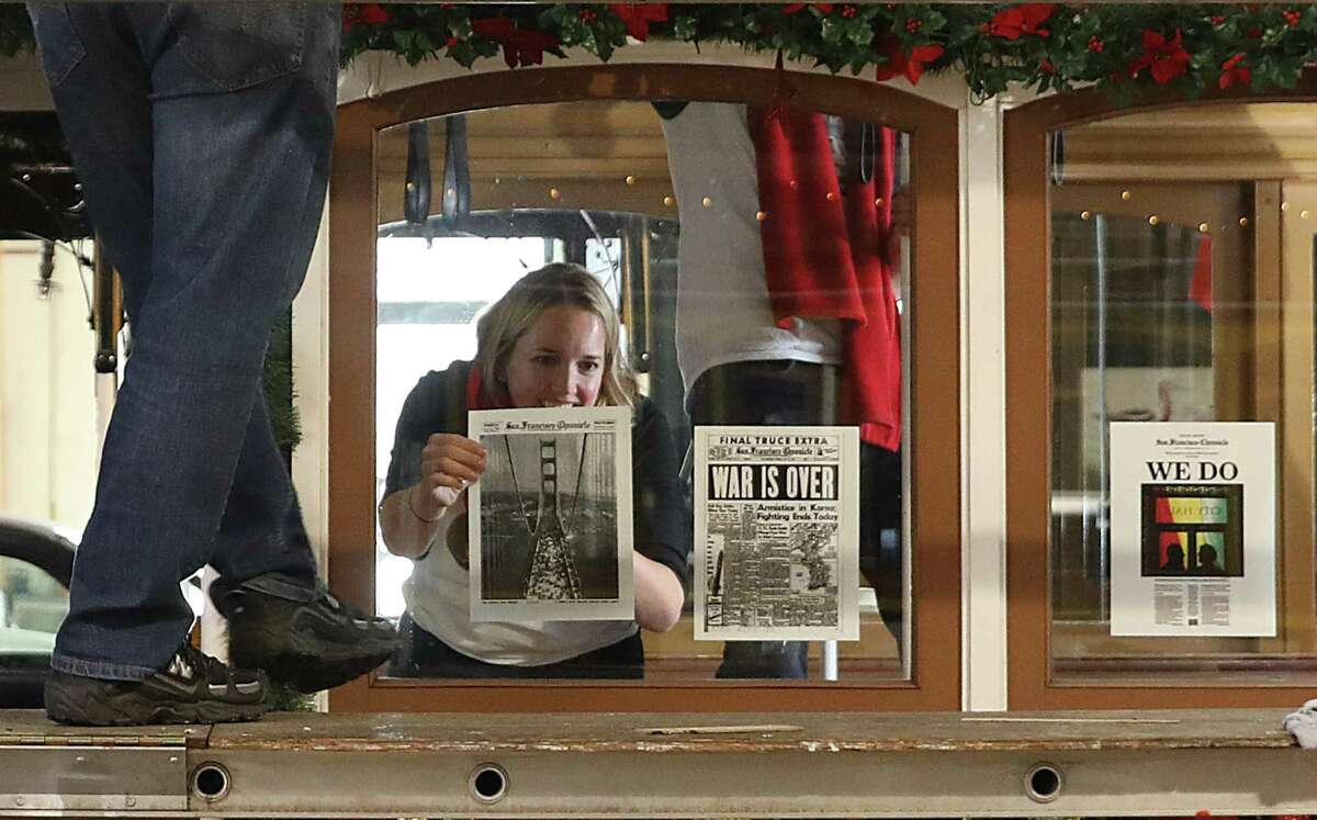 Heather Knight decorates a cable car with copies of historic Chronicle front pages.