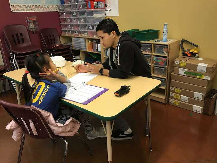 Teacher Omega Pascubello helps Kylie Chen with her math homework at an after school program at the Maureen and Craig Sullivan Youth Center run by Catholic Charities of San Francisco.