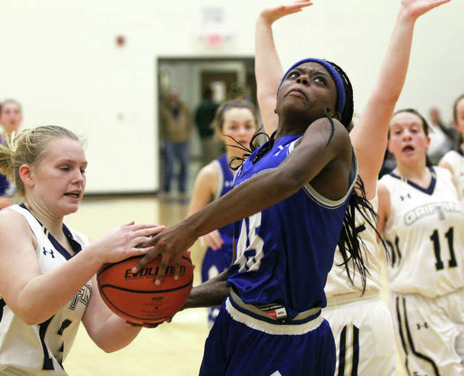 Marquette Catholic's Adrenna Snipes (middle) has the ball stripped way on by Father McGivney's Rachel Maller, who was whistled for a foul in the play in the first half Thursday night at Father McGivney High School in Glen Carbon. Photo: Greg Shashack / The Telegraph