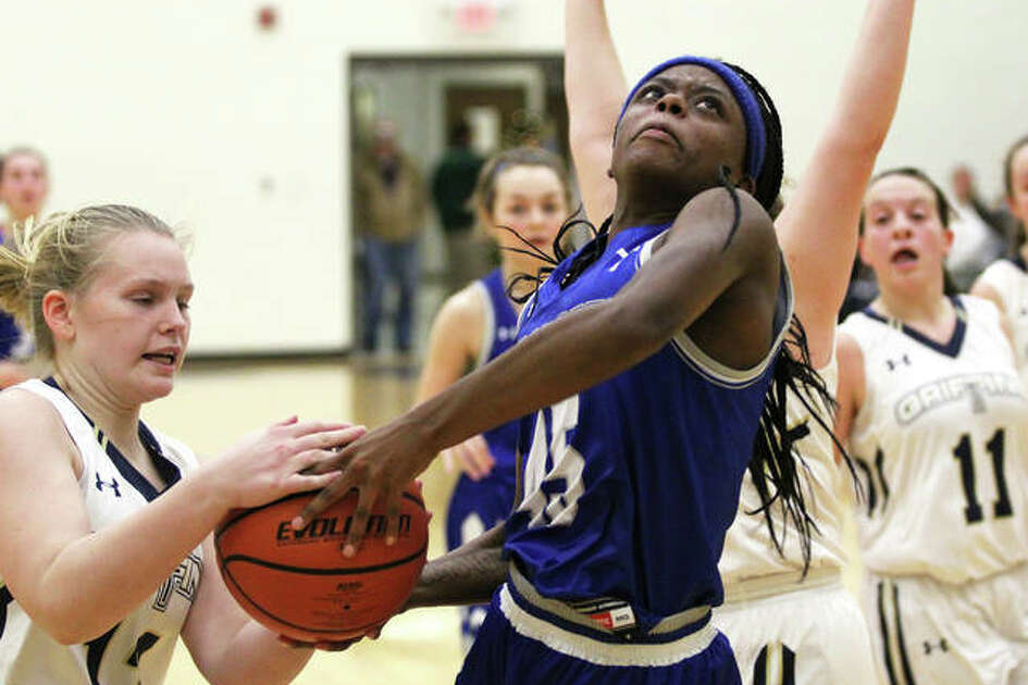 Marquette Catholic's Adrenna Snipes (middle) has the ball stripped way on by Father McGivney's Rachel Maller, who was whistled for a foul in the play in the first half Thursday night at Father McGivney.